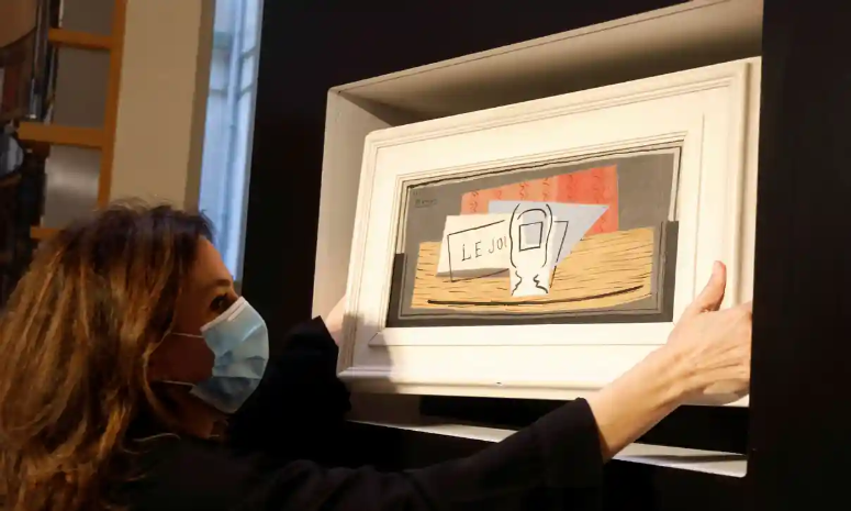 Photo of woman taking a picasso painting off the shelf