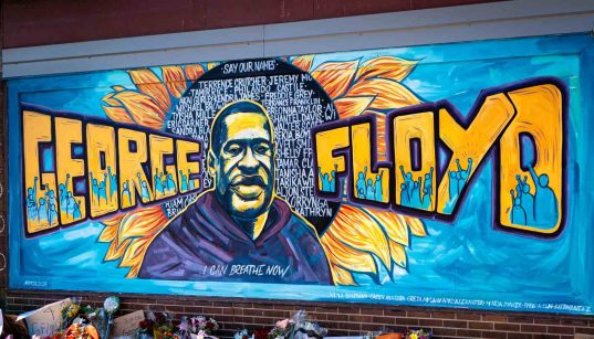 A mural of george floyd spray painted on a wall